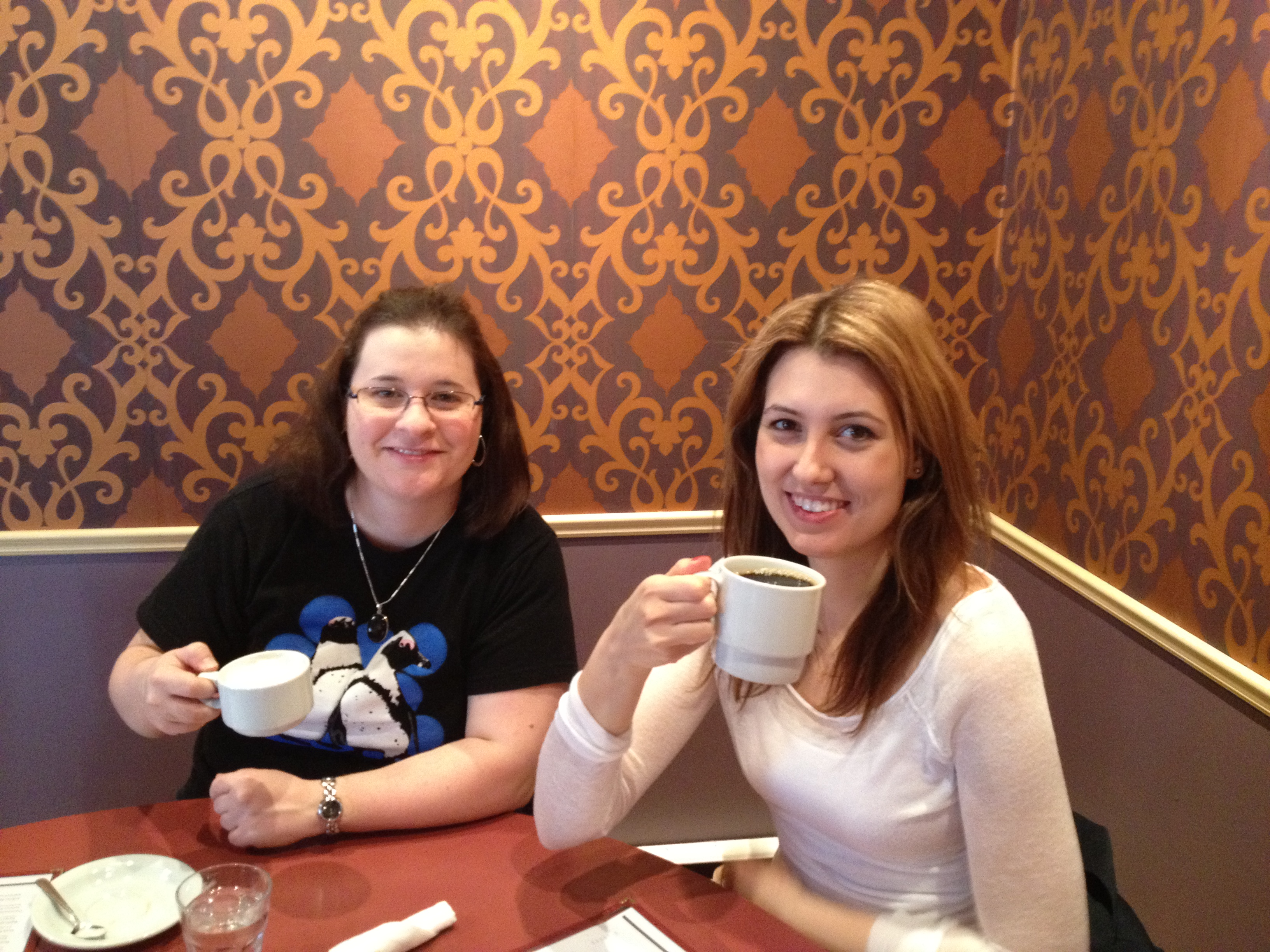 Linds and Monika posing with their coffees against a very 70s wallpaper