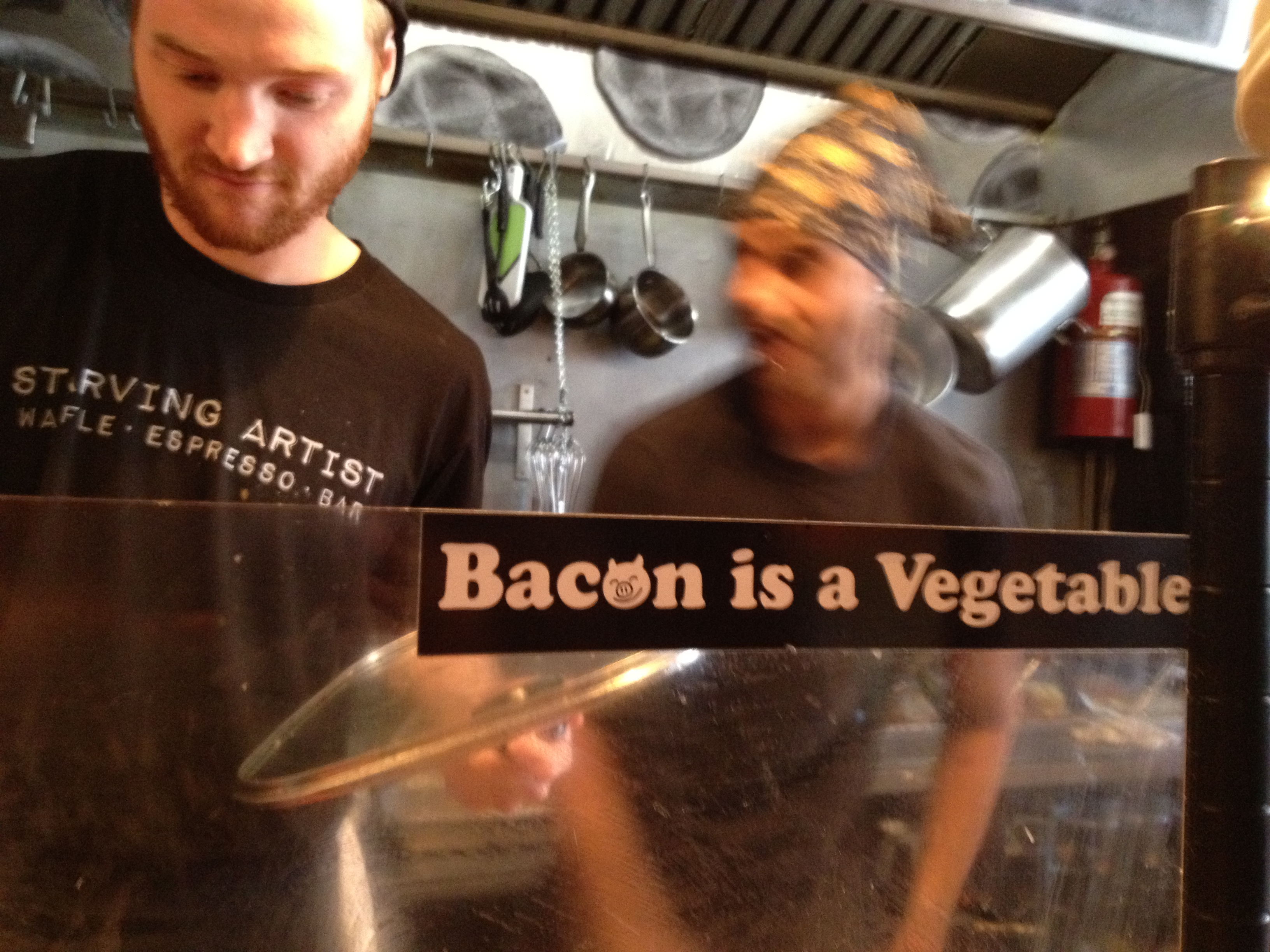 "Cooks busy cooking in an open kitchen with an awesome sign saying ""Bacon is a Vegetable"".  This is my new mantra"